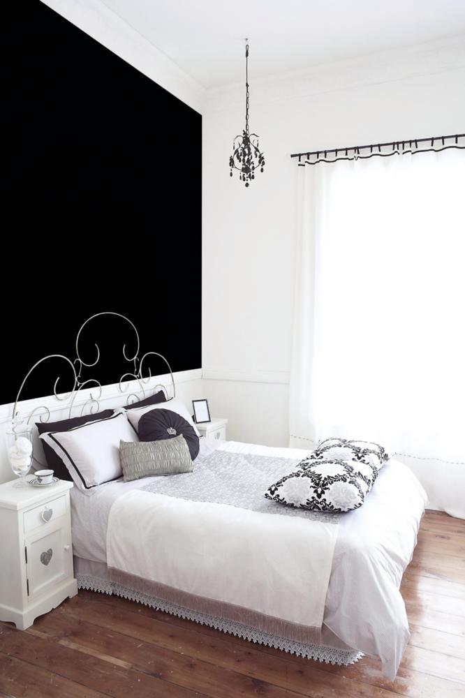 black wall behind the bed in the old building interior