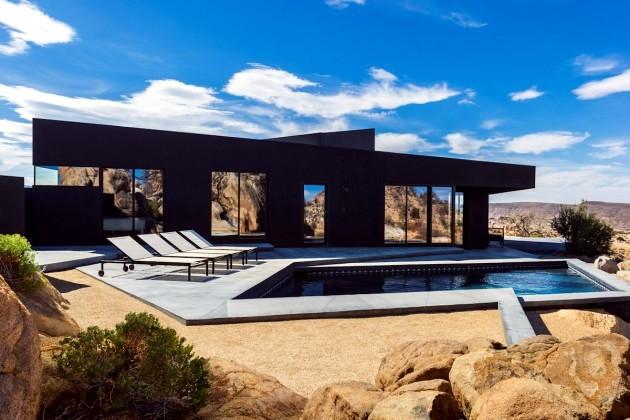 A black modern home in the California desert