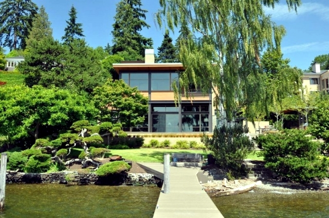 Modern House On The Lake With A Flat Green Roof And