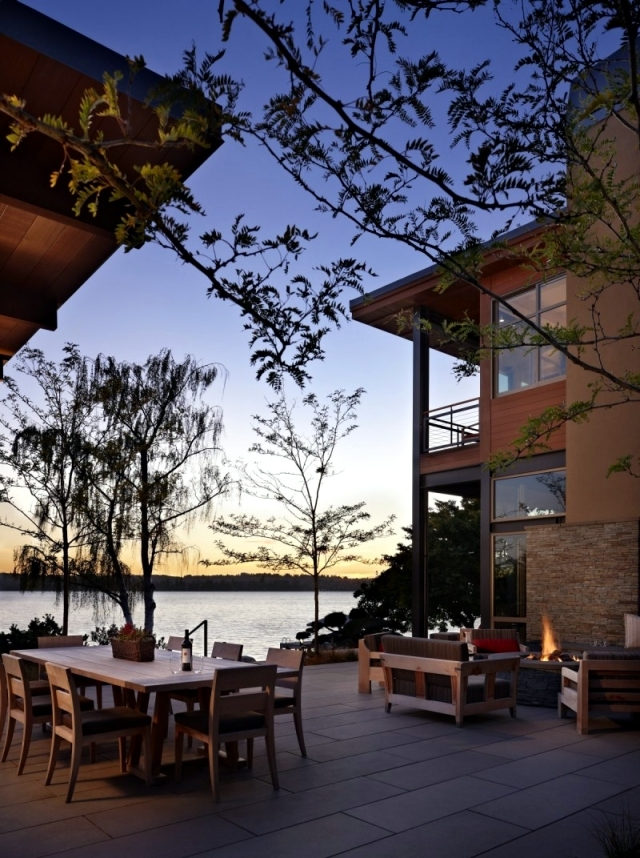 Modern house on the lake with a flat green roof and a fantastic view