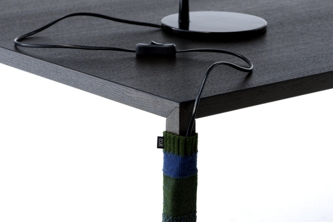 Knitted sock serves as a cable concealment for desktop design