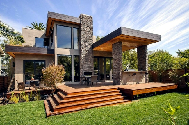 modern massive house with stone facade and a bright