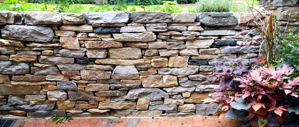 Stone wall in the garden slope stabilization, which provides visual and noise